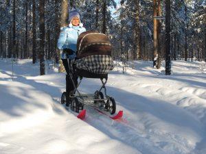 Lastenvaunut, joissa sukset, lumisessa metsässä.