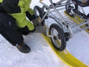 Henkilö asentaa suksia lastenvaunujen renkaiden alle.